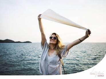 Chica sonriente frente al mar con un pañuelo en las manos